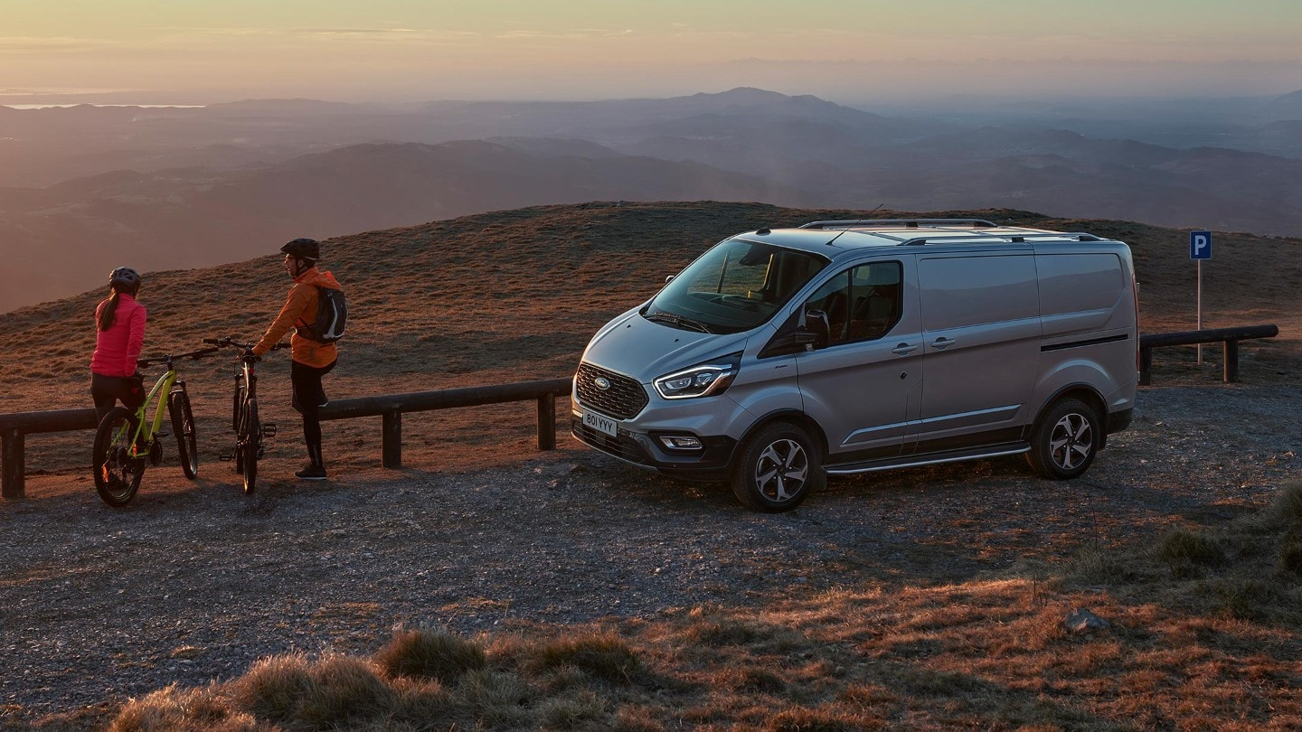 Ford Transit Custom Active side view with closed door against sunset and two cyclists