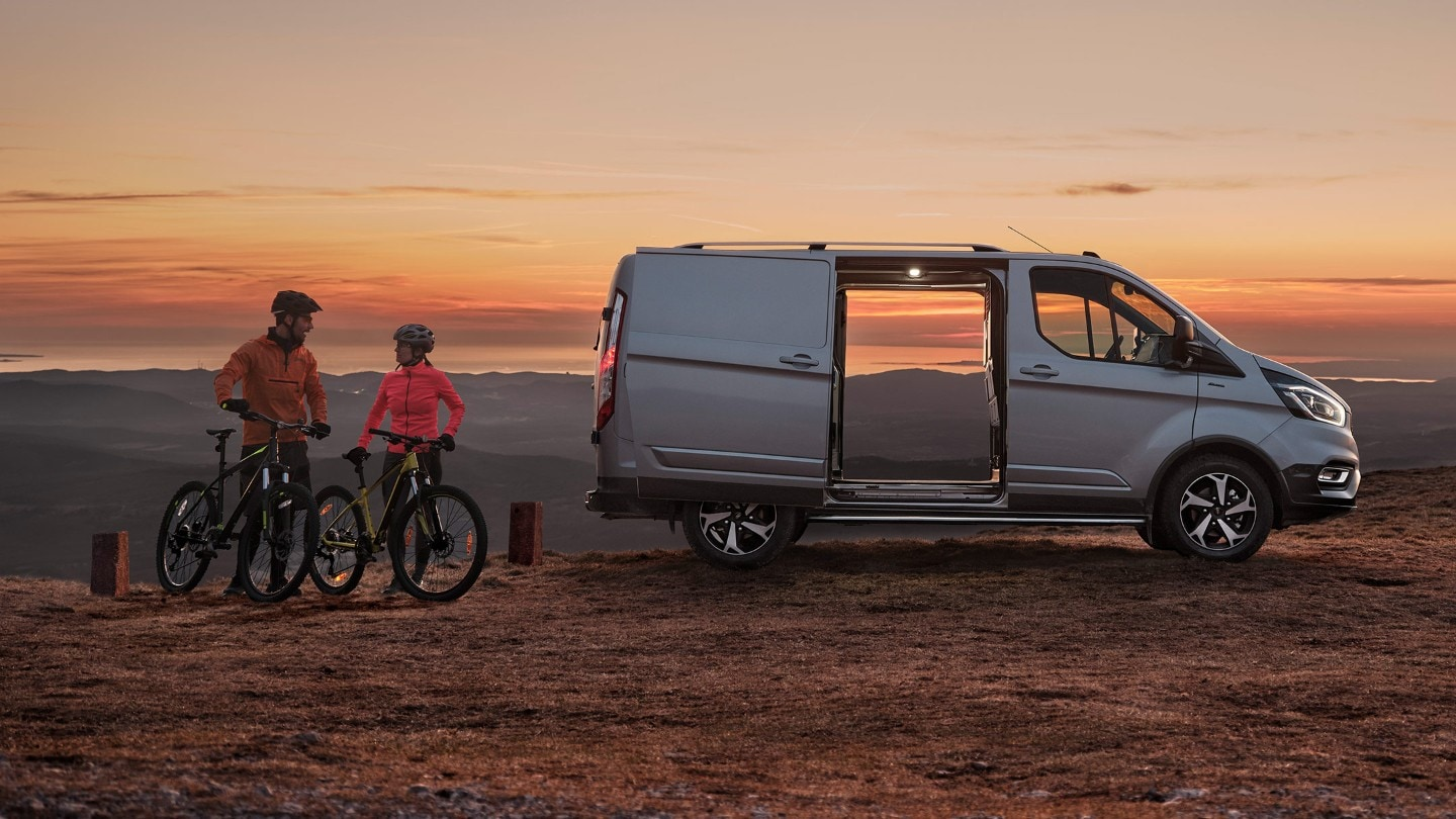 Ford Transit Custom Active side view with open door against sunset and two cyclists